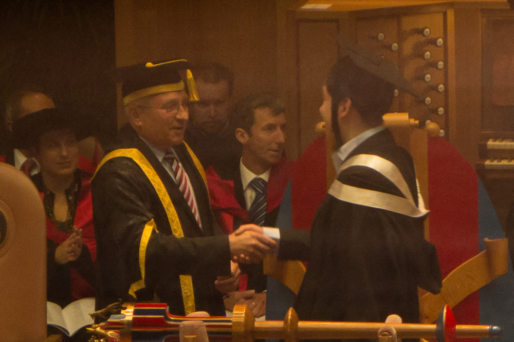 I promise you, this is a photo of me shaking the hand of the Dean at my graduation ceremony, not just a noisy, slightly out-of-focus shot of people in some funny hats. But it's that too, of course.